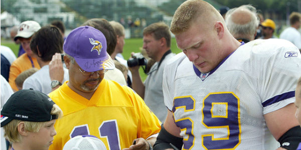 Brock Lesnar signs an autograph for a Minnesota Vikings fan at training camp.