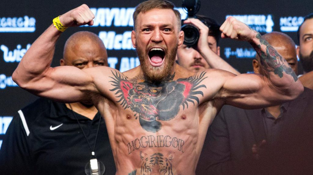 Conor McGregor flexes his muscles and roars during a UFC weigh in