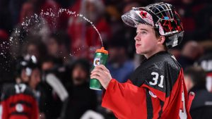 carter hart squirts a stream of h2o from his gatorade water bottle during a game for canada