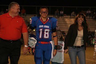 Collin Saring stands smiling with his parents on Senior Night in high school.