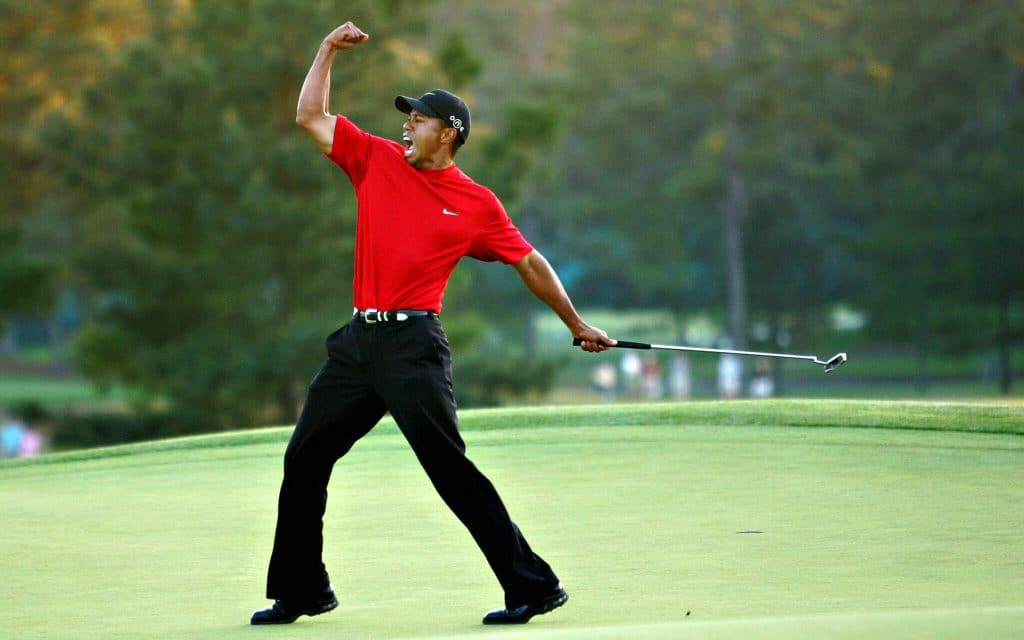 Tiger Woods pumps his fist at the 2001 Masters, donning his trademark red Nike golf shirt.