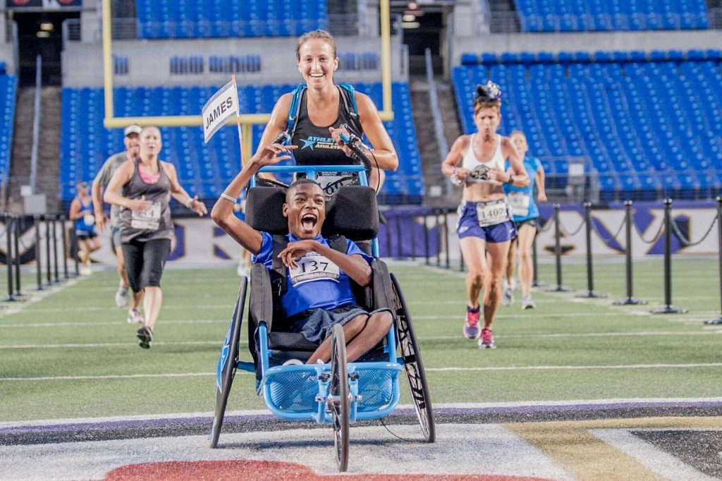 An ASA athlete celebrates as he crosses the finish line in an NFL stadium