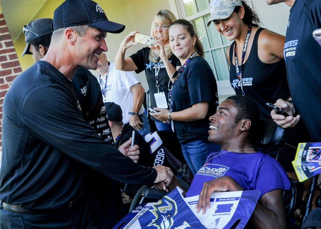 Ravens head coach John Harbaugh greets an ASA athlete at a training camp practice