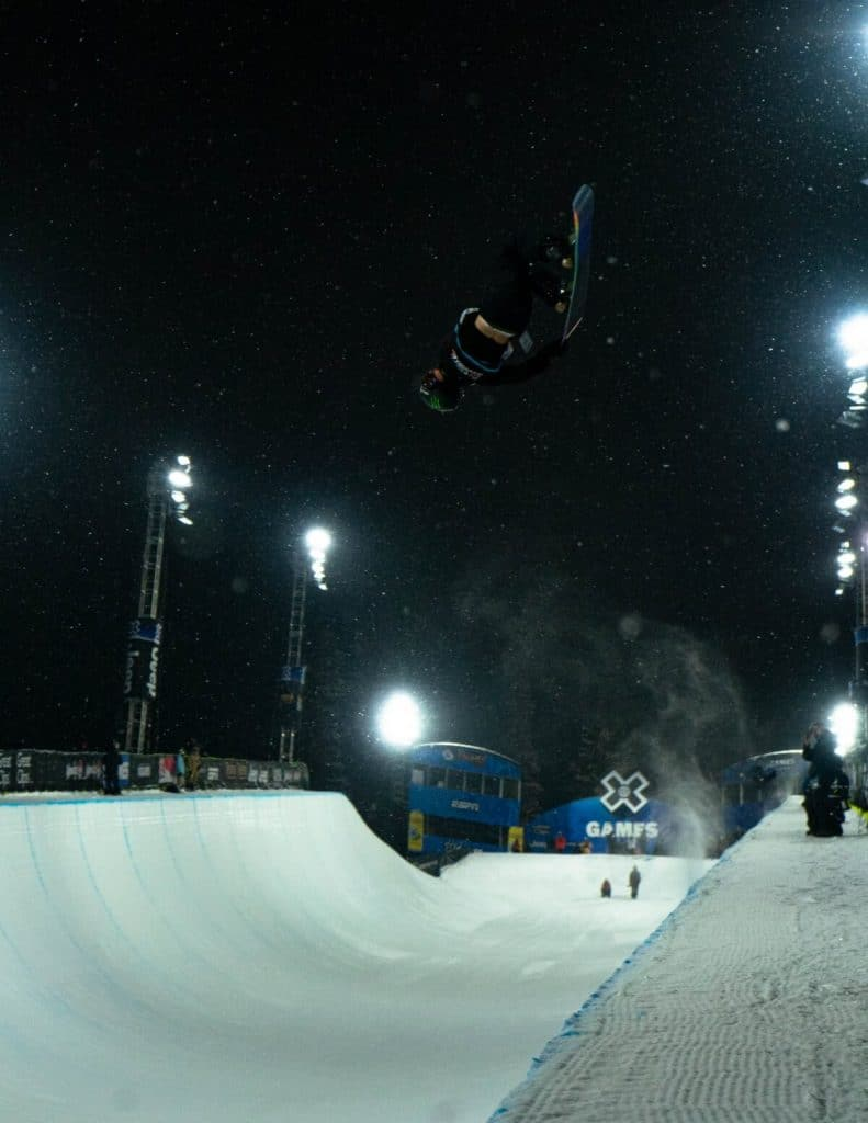Lucas Foster flipping at top of halfpipe on mountain in the snow